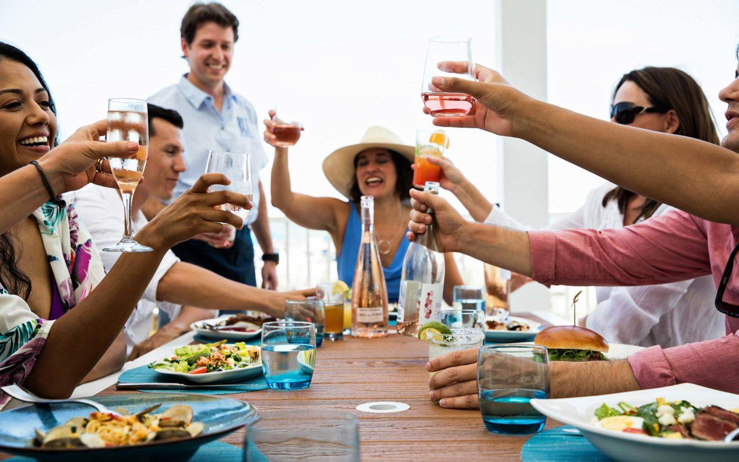 a group of people dressed in summer clothes and raising their glasses in a cheers at Blu Restaurant and Bar